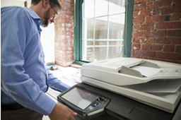 man using small copier in an office with brick wall