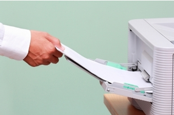 business person putting paper into small copier