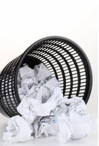 wadded up paper balls in tipped over black trash bin