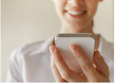 woman smiling at white smartphone in hand