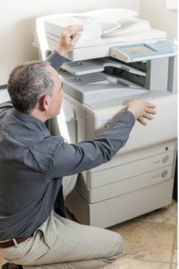 man kneeling and looking at copier