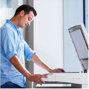 man using scanner on a multi-function copier