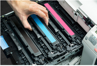 man pulling out ink cartridge from copier