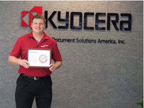 Jason Huff standing in front of Kyocera sign holding award