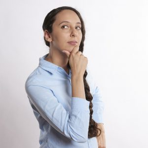 woman in blue shirt thinking about which copier to buy for business