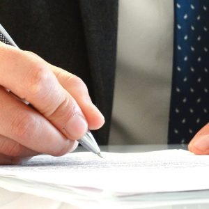man in suit signing a document